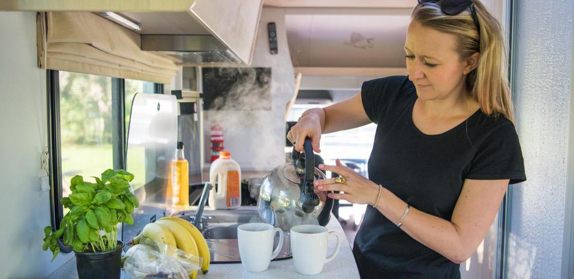 Woman Holding Kettle - RV Rental Canberra - Campervan Rental Shop